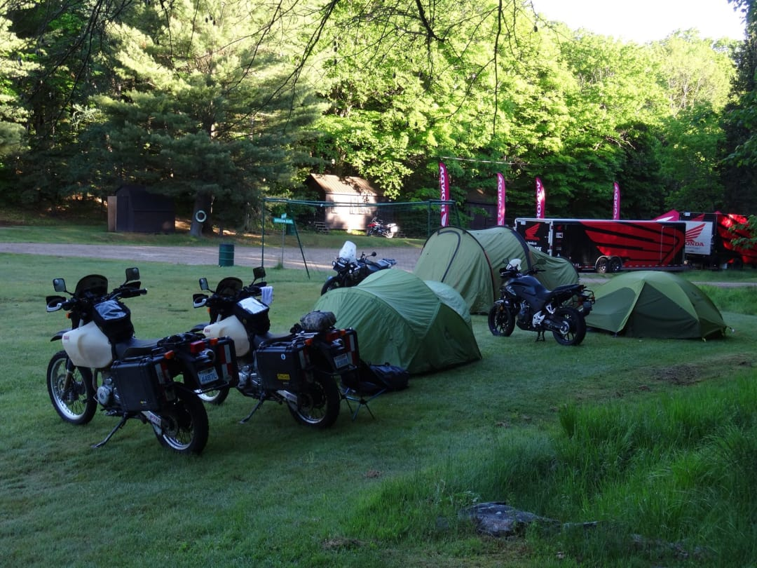Several motorcycles and tents in a campground