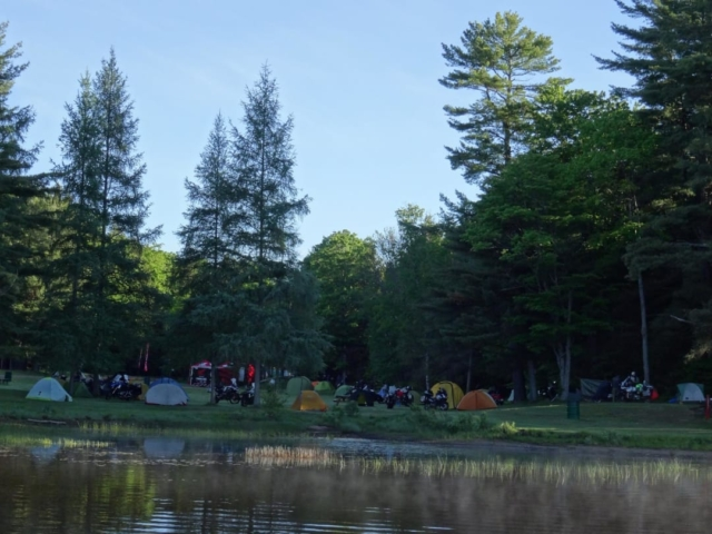 Many tents and motorcycles in a camp ground setting