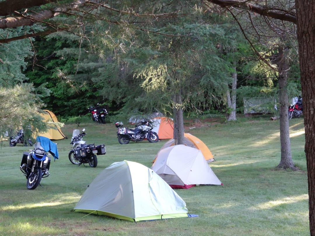 Several tents and motorcycles in a camp ground at dawn