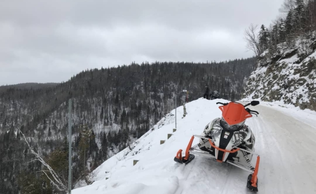 A snowmobile stoped on a trail beside a cliff hundreds of feet above a valley