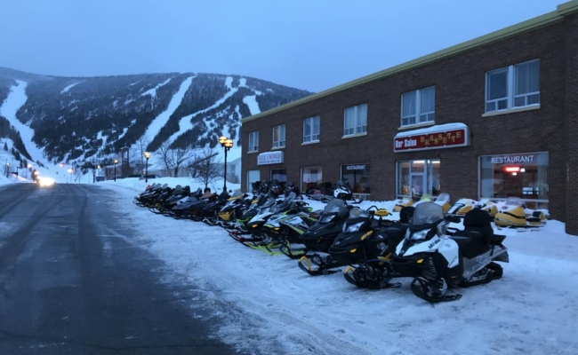 27 snowmobiles lined up in front of the Copper Hotel in Murdochville, Qc