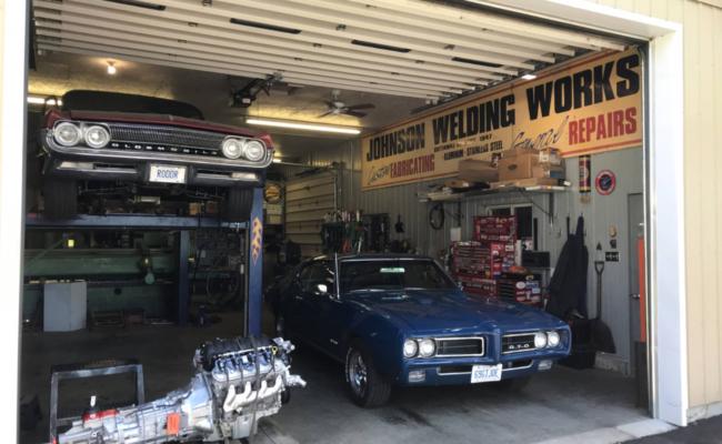 Photo of a blue Pontiac GTO in a garage awaiting repairs