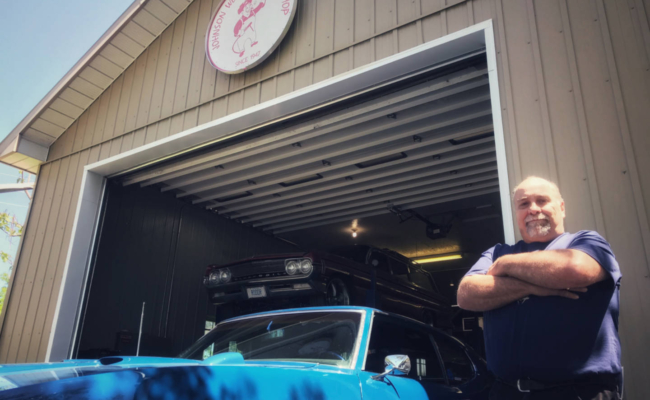 Photo of a mechanic standing beside a blue Pontiac GTO