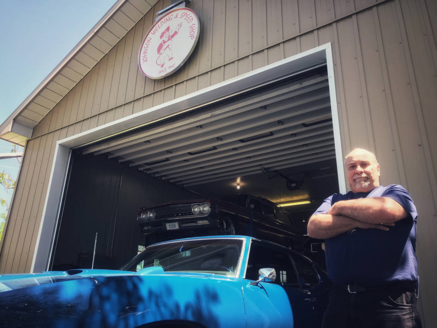 Photo of a mechanic standing beside a blue Pontiac GTO