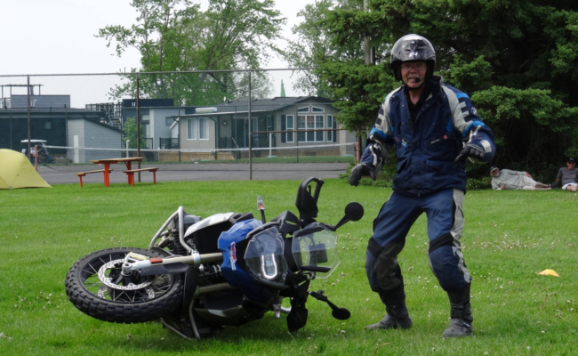 A photo of a man standing beside a fallen motorcycle
