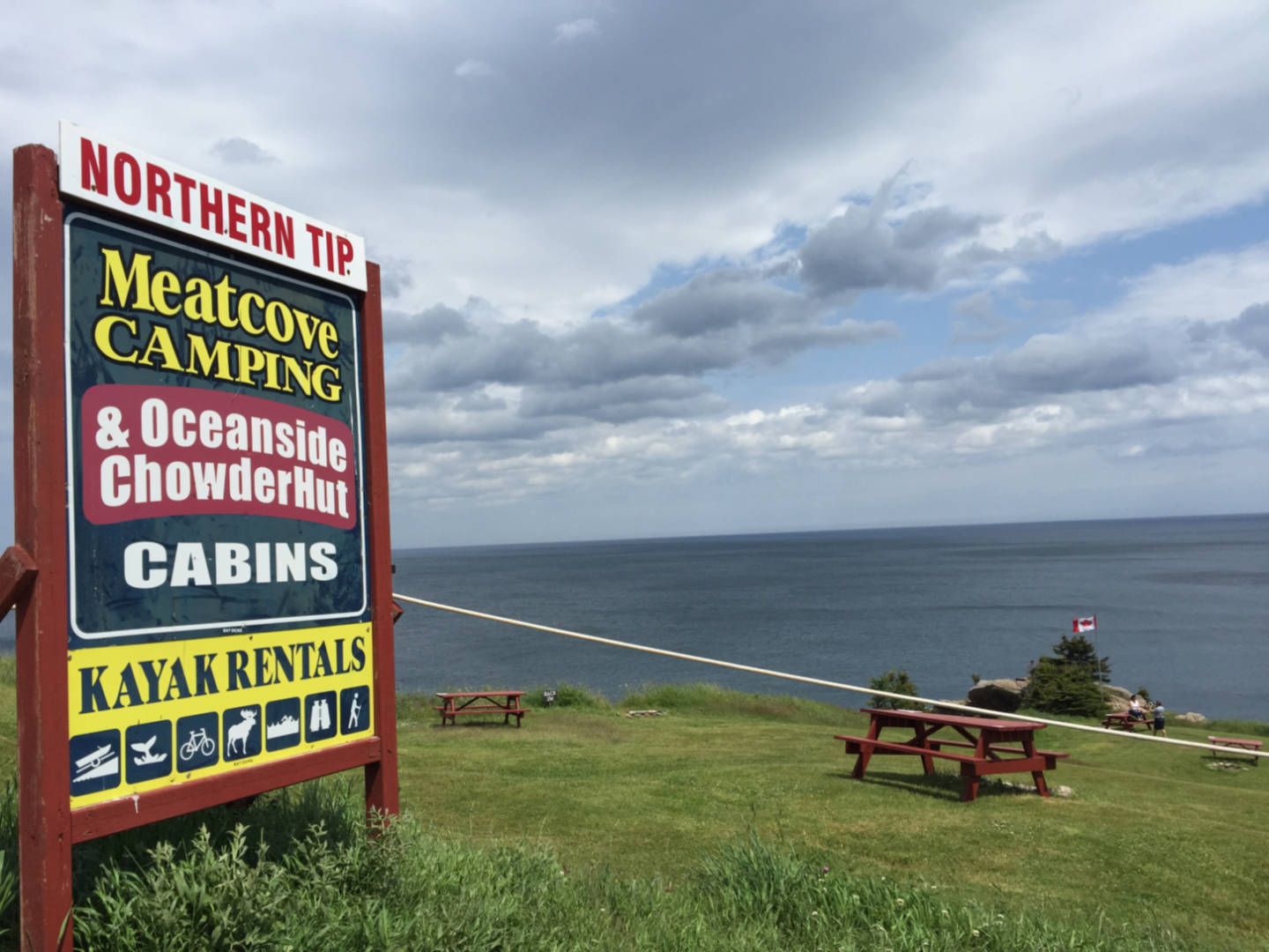 A photo of the sign and picnic tables at Meat Cove campground