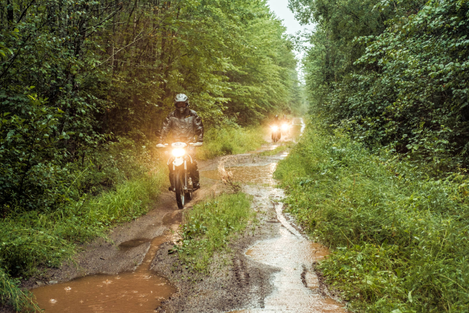 a photo of motorcycles riding in mud and rain at the Fundy Adventure Rally