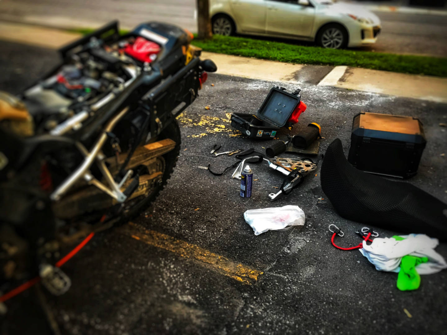 a photo of a Suzuki motorcycle being repaired in a parking lot