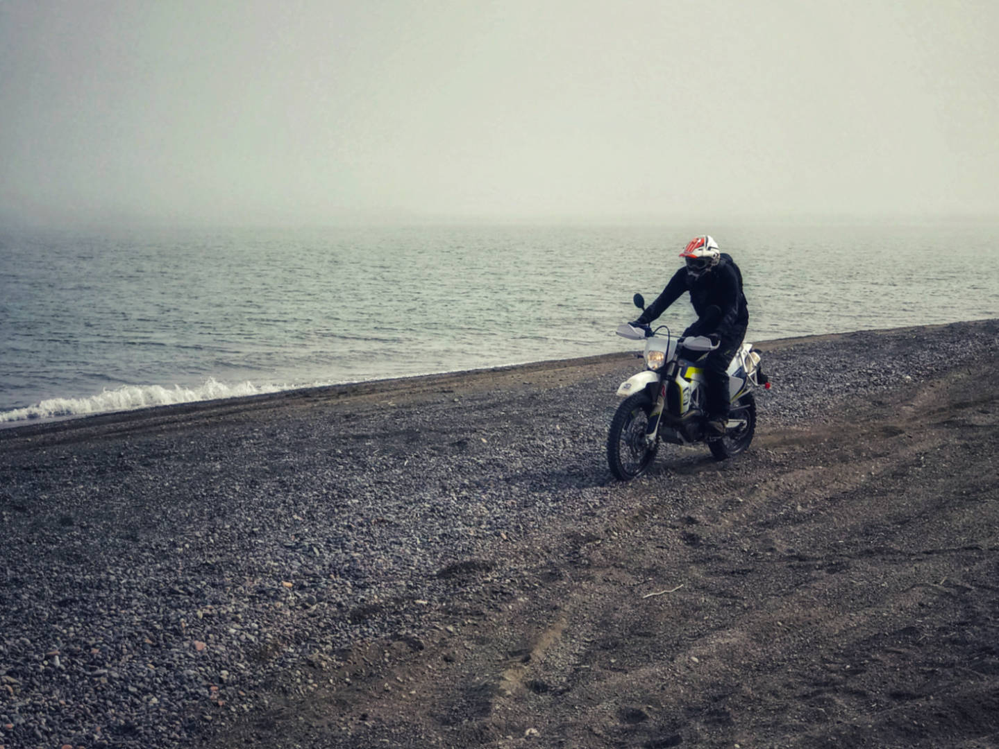 A photo of a Husqvarna enduro motorcycle on the beach at Martins Head, NB