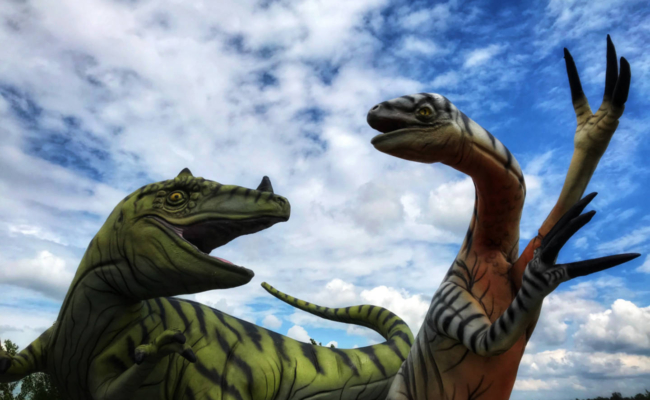 photo of 2 life-sized fiberglass dinosaurs fighting at Le Madrid Quebec