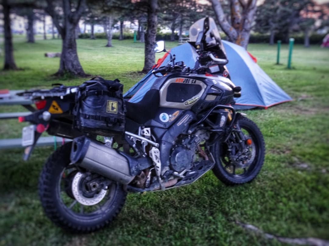 A Suzuki V-Strom parked in front of a blue tent at Linkletter Provincial Park