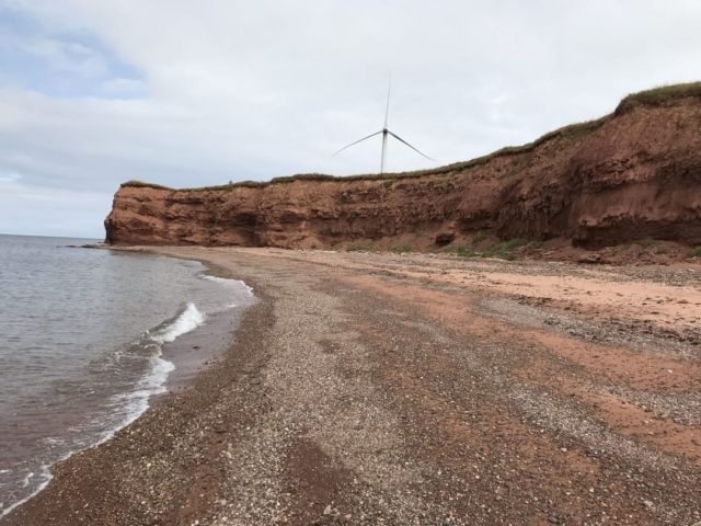 A wind turbine above the sea cliffs at North Cape beach PEI