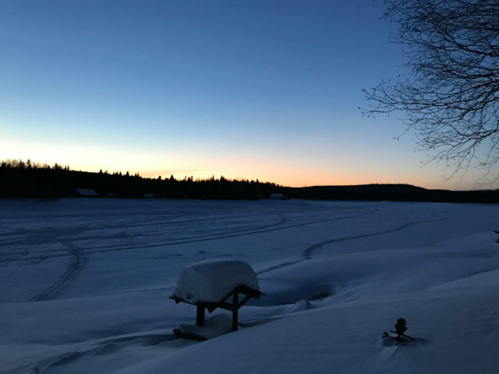 a photo of sunset in winter over a snow covered lake