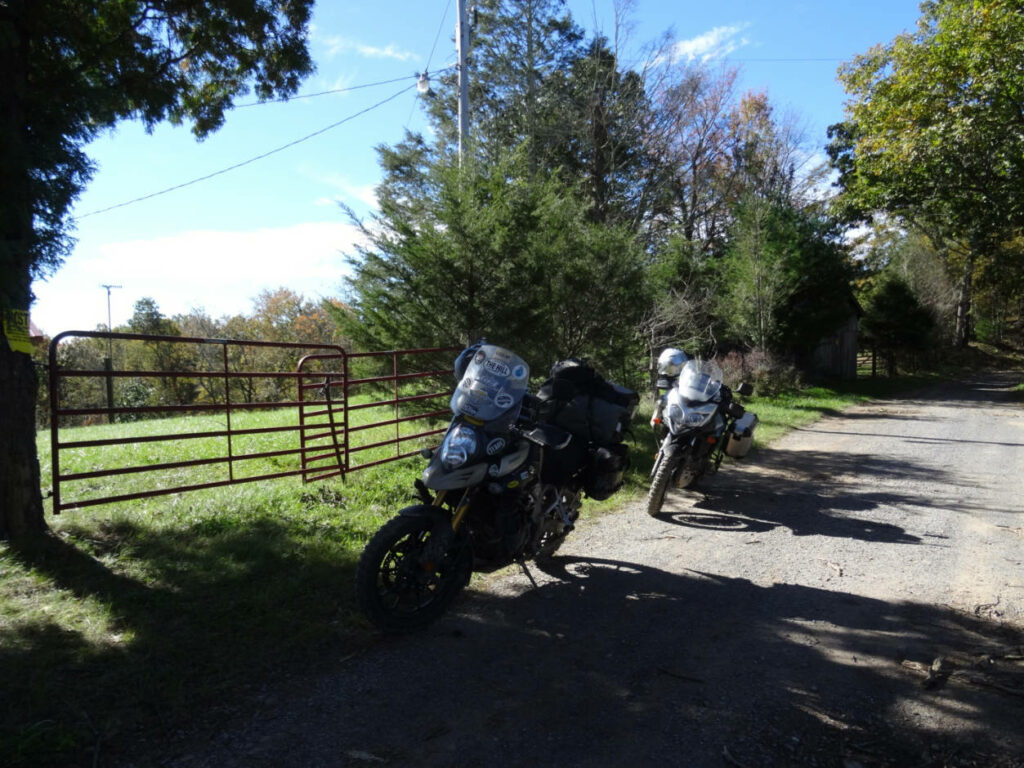 2 adventure style motorcycles on a forested gravel road
