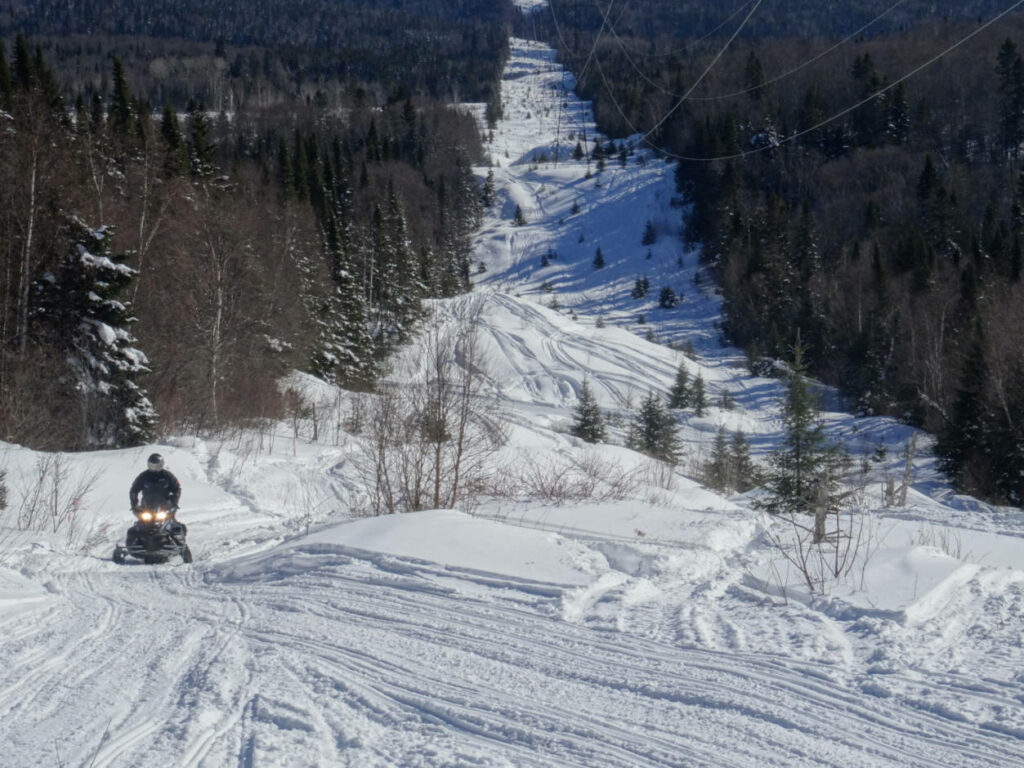 a photo of a snowmobile on a trail following a hydro line
