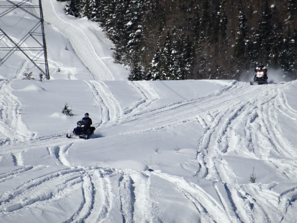 a photo of 2 snowmobiles on the trail on a mountainside