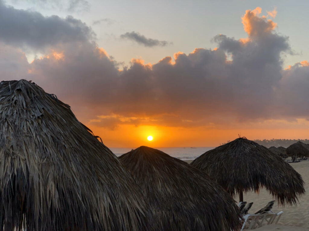 a photo of the sunrise over some grass huts in the caribbean