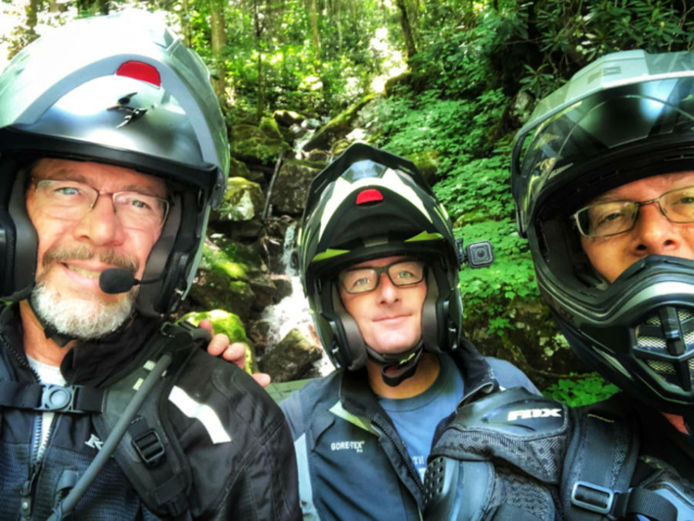 a photo of 3 motorcycle adventure riders in front of a waterfall on the MABDR
