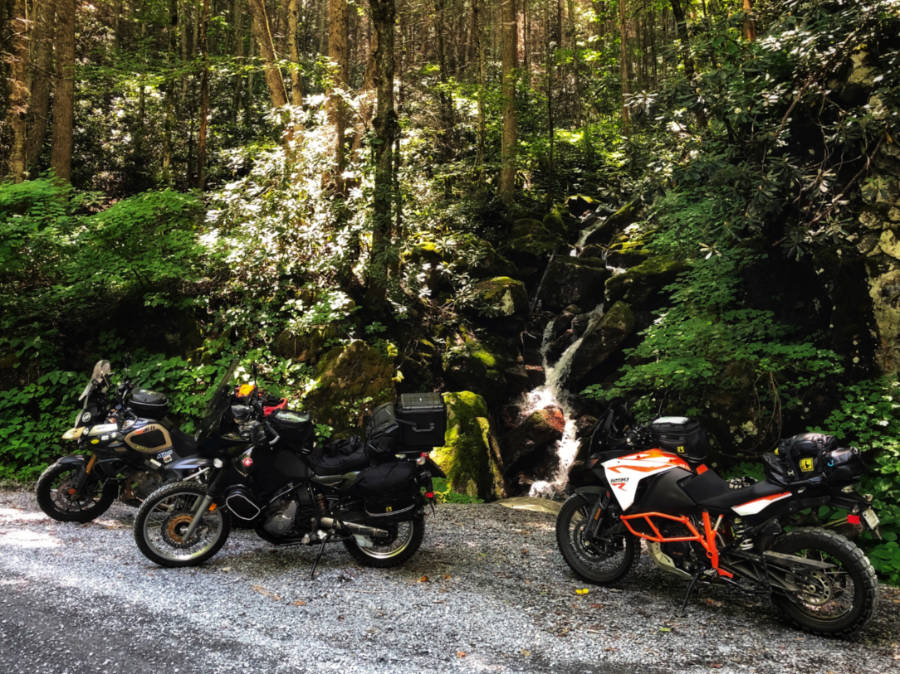 a photo of 3 adventure motorcycles in front of a waterfall on the MABDR