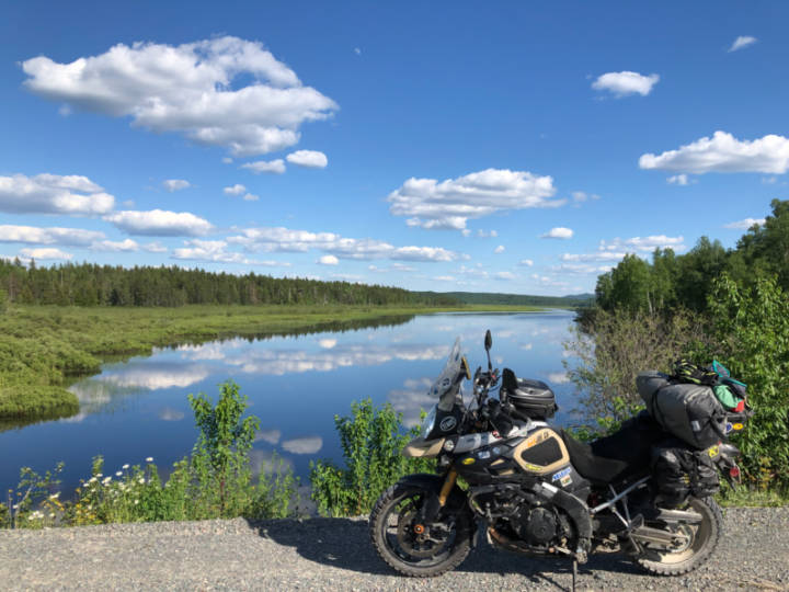 a photo of a motorcycle on a gravel road in front of a lake